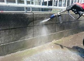高圧洗浄機でコンクリートの塀の汚れを洗浄している写真