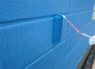 ブロック塀に上塗りを重ねてる写真