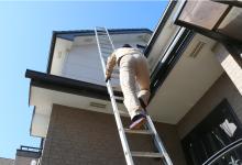 はしごをかけて屋根に上る現場調査スタッフ